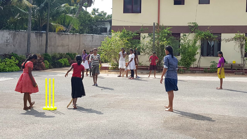 Girls playing cricket in the playground