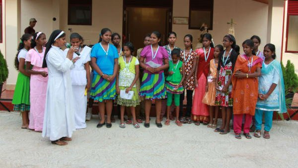 group photo of girls and nuns in front of the home